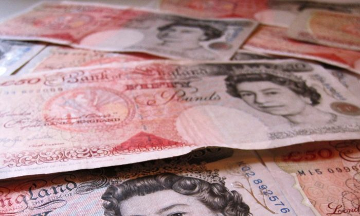 """A woman from Bolton U.K. was sentenced to two years in prison for tricking her husband's family out of over $64,000. (""""£50 notes"""" by Images Money/Flickr [CC BY 2.0 (ept.ms/2haHp2Y)])"""