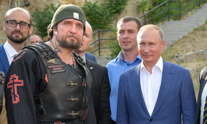 Leader of the Night Wolves Russian motorcycle club Alexander Zaldostanov stands beside Russia's President Vladimir Putin at the 35th Coastal Defence Battery memorial center in central Sevastopol on the Crimea Peninsula on Aug. 18, 2017.  Zaldostanov and the Night Wolves have opposed democratic movements in Ukraine and have rallied Russian sentiments there to support Moscow and rebel forces. (ALEXEY DRUZHININ/AFP/Getty Images)