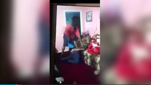 A screenshot of video of a man standing over a girl with what looks like a belt, hitting her for downloading snapchat on her phone. (Screenshot via Youtube/OMG 2.0 )