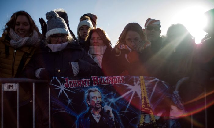 Fans attend a tribute ceremony to the late French singer and actor Johnny Hallyday near the Madeleine Church during a 'popular tribute' in Paris, France, December 9, 2017.  (Reuters/Yoan Valat/Pool)