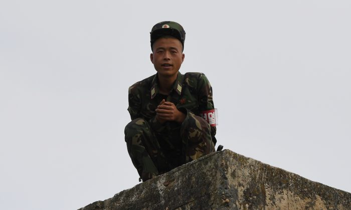 A North Korean soldier chats with a Chinese boat driver as he crouches on a wall on the bank of the Yalu river near the North Korean town of Sinuiju, opposite the Chinese border city of Dandong. (Greg Baker/AFP/Getty Images)
