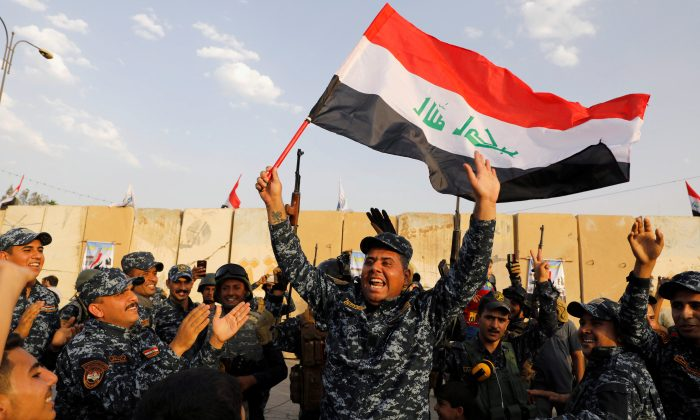 A member of Iraqi Federal Police waves an Iraqi flag as they celebrate victory of military operations against the ISIS terrorists in West Mosul, Iraq, on July 2, 2017. (Reuters/Erik De Castro/File Photo)