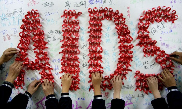 Chinese students use handmade red ribbons to form 'AIDS' one day ahead of the the World AIDS Day, at a school in Hanshan, east China's Anhui province on Nov. 30, 2009. (STR/AFP/Getty Images)