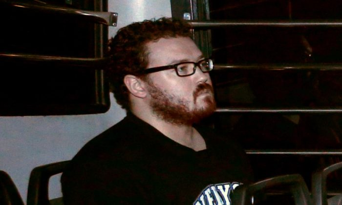 Rurik George Caton Jutting, a British banker charged with two counts of murder after police found the bodies of two women in his apartment, sitting in the back row of a prison bus as he arrives at the Eastern Law Courts in Hong Kong Nov. 24, 2014. (Reuters/Bobby Yip/File Photo)