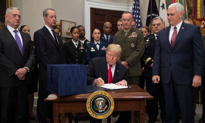President Donald Trump, surrounded by military officials and members of Congress, including Vice President Mike Pence (R) and Secretary of Defense Jim Mattis (L), signs H.R. 2810, National Defense Authorization Act for Fiscal Year 2018, in the Roosevelt Room at the White House in Washington, DC, Dec. 12, 2017. (SAUL LOEB/AFP/Getty Images)