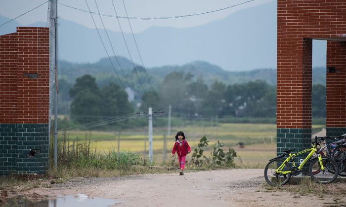 A schoolgirl walks along the street in Pingjiang County in China's Hunan Province on Oct. 8, 2015. (Johannes Eisele/AFP/Getty Images)