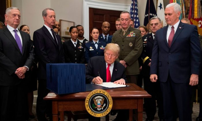 US President Donald Trump, surrounded by military officials and members of Congress, including Vice President Mike Pence (R) and Secretary of Defense Jim Mattis (L), signs H.R. 2810, National Defense Authorization Act for Fiscal Year 2018, during a signing ceremony in the Roosevelt Room at the White House in Washington, DC, Dec. 12, 2017. (SAUL LOEB/AFP/Getty Images)