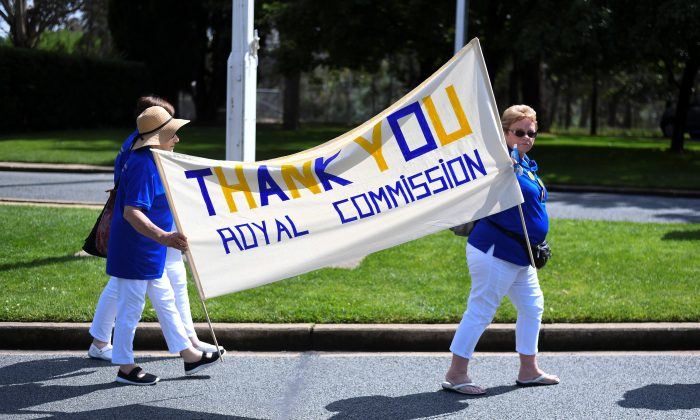Members of the Care Leavers Australasia Network (CLAN) hold up a banner thanking the Commission as they await the final report from the Royal Commission into Institutional Responses to Child Sexual Abuse outside Government House in Canberra, Australia, Dec. 15, 2017. (AAP/Lukas Coch/via Reuters)