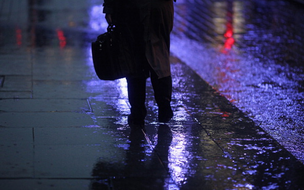 A man walks through a rain shower in Scotland in this file photo. A homeless man has been hailed a hero after he stood in the pouring rain for hours to guard cash left in a stranger's open car in Glasgow on Dec. 14. (Jeff J Mitchell/Getty Images)