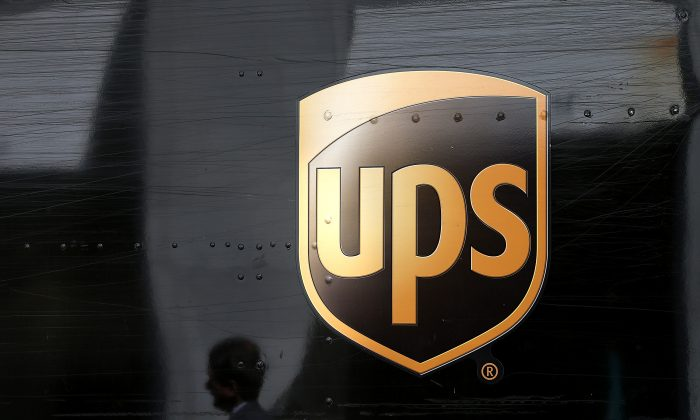 A pedestrian walks by a United Parcel Service (UPS) truck in San Francisco, California on June 17, 2014. (Photo by Justin Sullivan/Getty Images)