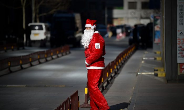 A salesman dressed as Santa Claus waits for customers at the entrance of a shop in Beijing on December 25, 2014. (Wang Zhao/AFP/Getty Images)