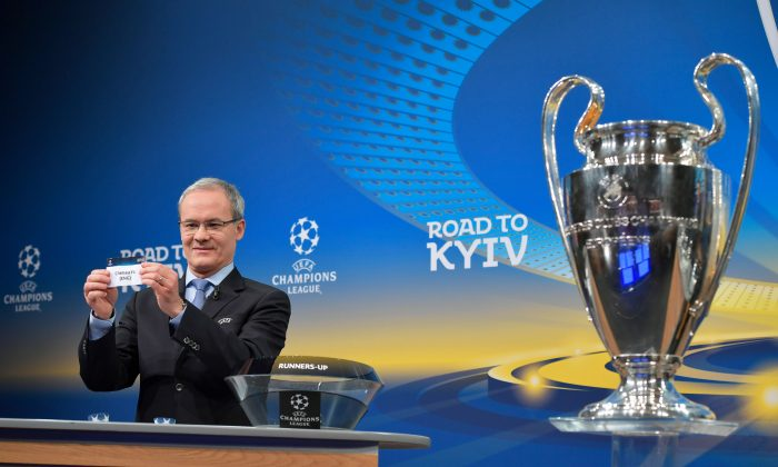 UEFA director of competitions Giorgio Marchetti shows the slip of Chelsea FC next to the Champions League trophy during the draw for the round of 16 of the UEFA Champions League football tournament at the UEFA headquarters in Nyon on Dec 11, 2017. (Fabrice Coffrini/AFP/Getty Images)