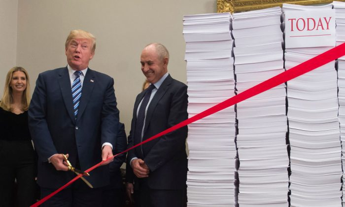 President Donald Trump holds gold scissors as he prepares to cut a red tape tied between two stacks of papers representing the government regulations of the 1960s and the regulations of today after he spoke about his administration's efforts in deregulation in the Roosevelt Room of the White House in Washington on Dec. 14, 2017. (Saul Loeb/AFP/Getty Images)
