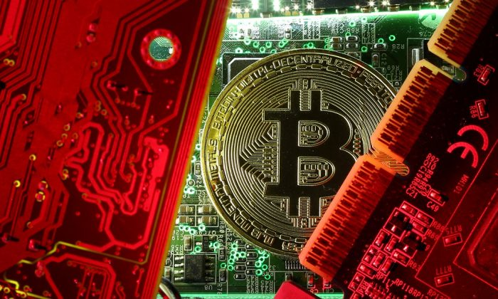 A coin representing the bitcoin cryptocurrency is seen on computer circuit boards in this illustration picture, October 26, 2017. (REUTERS/Dado Ruvic/File Photo)