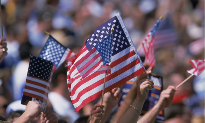 American Flags are waved by the crowd at the Rose Bowl in Pasadena, California, on Sept. 22, 2001. (Stephen Dunn/Allsport)