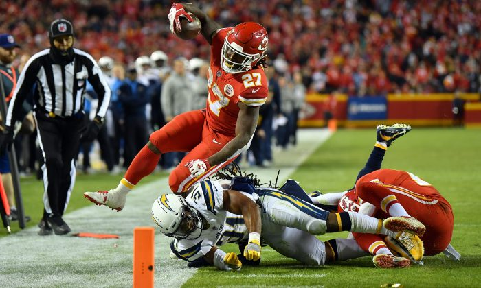 Running back Kareem Hunt #27 of the Kansas City Chiefs carries the ball as free safety Adrian Phillips #31 of the Los Angeles Chargers knocks him out-of-bounds before reaching the endzone during the game at Arrowhead Stadium in Kansas City, Missouri, on Dec. 16, 2017. (Peter Aiken/Getty Images)
