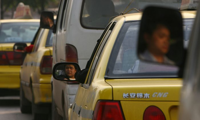 In this file photo dated on April 18, 2006, drivers wait in a line to fuel their cars at a natural gas filling station in Chongqing City, China. (China Photos/Getty Images)
