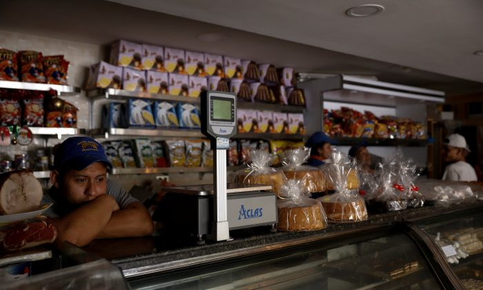 A vendor waits in darkness inside a bakery, during a massive blackout in Caracas, Venezuela Dec. 18, 2017. (Reuters/Marco Bello)