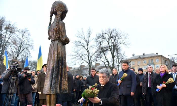 Ukrainian President Petro Poroshenko lays spikelets of wheat on the Holodomor memorial in Kiev on November 25 during a ceremony in memory of the victims of the Holodomor famine. The 1932-33 famine took place as harvests dwindled and Soviet leader Josef Stalin's police enforced the brutal communist policy of collectivizing agriculture by requisitioning grain and other foodstuffs. (GENYA SAVILOV/AFP/Getty Images)