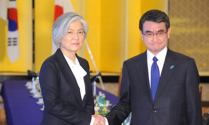 South Korean Foreign Minister Kang Kyung-wha (L) shakes hands with her Japanese counterpart Taro Kono as they attend the Japan-ROK Foreign Minister meeting at the Ministry of foreign affairs in Tokyo on Dec. 19, 2017. (DAVID MAREUIL/AFP/Getty Images)