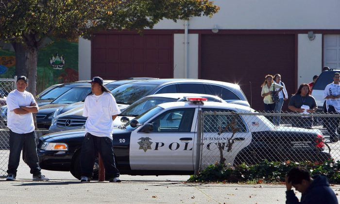 Youths stand near a police car that is parked in front of Richmond High School on Nov. 2, 2009 in Richmond, California.   (Justin Sullivan/Getty Images)