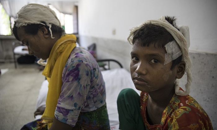 Rohingya Muslim refugee Dildar Begum, 30, recovers from her wounds alongside her daughter Nurkalima, 10, at a hospital in Cox's Bazar, Bangladesh on Sept. 15, 2017. Nearly 650,000 Rohingya refugees have fled into Bangladesh since late August during the outbreak of violence in the Burma's Rakhine State. (Paula Bronstein/Getty Images)