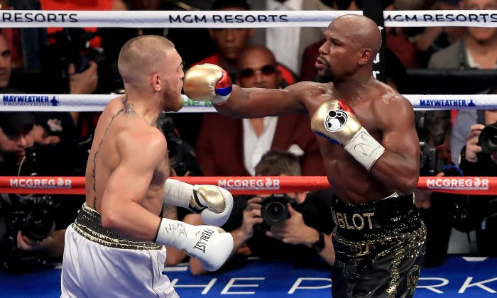 Floyd Mayweather Jr. (R) throws a punch at Conor McGregor during their super welterweight boxing match on Aug. 26, 2017, at T-Mobile Arena in Las Vegas, Nevada. (Sean M. Haffey/Getty Images)