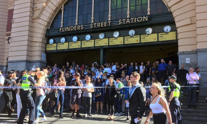 Members of the public stand behind police tape after Australian police said they have arrested the driver of a vehicle that ploughed into pedestrians at a crowded intersection near the Flinders Street train station in central Melbourne, Australia Dec. 21, 2017.  (Reuters/Melanie Burton)