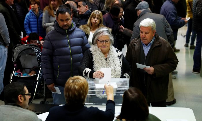 A woman casts her ballot as others wait to vote in Catalonia's regional elections at a polling station in Vic, Spain December 21, 2017. (Reuters/Juan Medina)