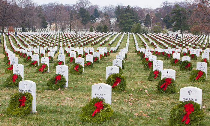 Volunteers with Wreaths Across America help place more than 100,000 remembrance wreaths on headstones at Arlington National Cemetery, Va., Dec. 13, 2013. The mission of Wreaths Across America is to remember and honor the fallen men and women of the armed forces by coordinating wreath laying ceremonies. (U.S. Army photo by Spc. James K. McCann)