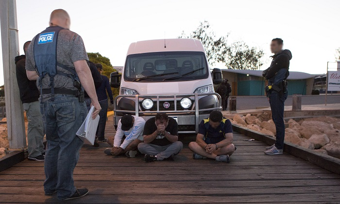 Australian police officers with three of the men arrested for the smuggling of 1.2 tonnes of methamphetamine into Australia. (Australian Federal Police)