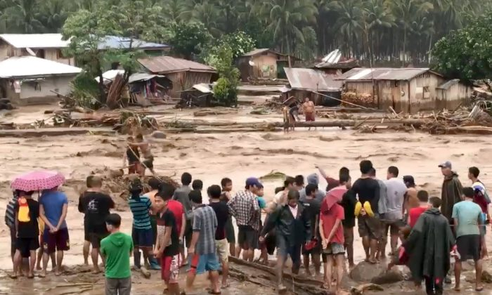 People help to rescue flood victims in Lanao del Norte, Philippines on Dec. 22, 2017 in this image taken from video footage obtained from social media. (Aclimah Cabugatan Disumala/via Reuters)