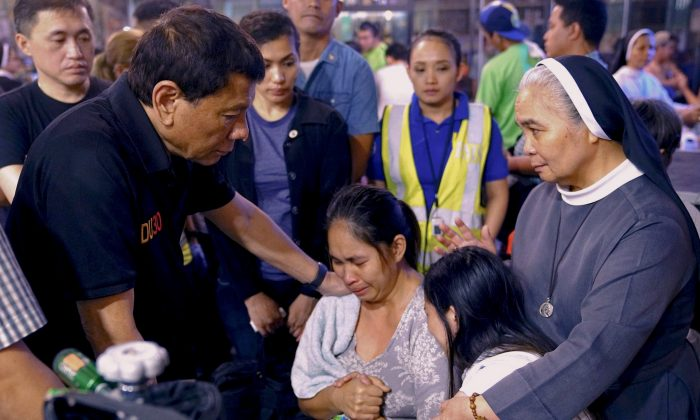 President Rodrigo Duterte comforts family members of fire victims in Davao city in Philippines on Dec. 24, 2017. (Reuters/Presidential Palace)