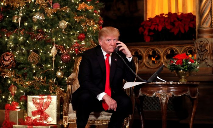 President Donald Trump participates in NORAD (North American Aerospace Defense Command) Santa Tracker phone calls with children at Mar-a-Lago estate in Palm Beach, Fla., on Dec. 24, 2017. (REUTERS/Carlos Barria)