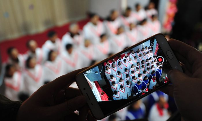 This photo taken on December 24, 2017 shows a participant taking a video as a choir sings hymns during a Christmas Eve mass at a church in Fuyang in China's eastern Anhui province. Reports from across China indicate that Christmas celebrations this year by Chinese Christians have been widely suppressed by the authority. (AFP/Getty Images)
