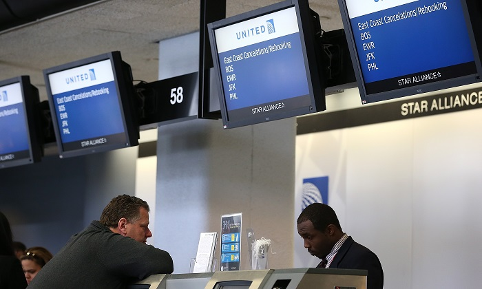 A file image of a United Airlines ticket agent helping a customer rebook a flight that was canceled due to weather at San Francisco International Airport, California. (Justin Sullivan/Getty Images)