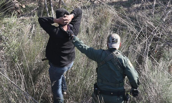 A Border Patrol agent leads an illegal alien out from the brush after capturing him near the U.S.–Mexico border at La Grulla, Texas, on Dec. 10, 2015. (John Moore/Getty Images)