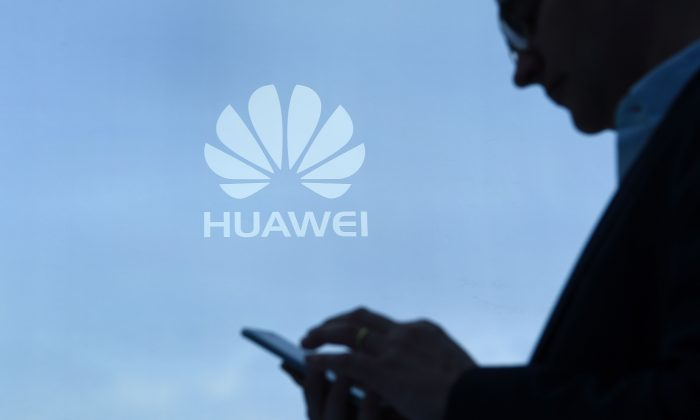 A man uses his mobile phone at the Huawei stand during the Mobile World Congress on February 28, 2017 in Barcelona, Spain. (Lluis Gene/AFP/Getty Images)