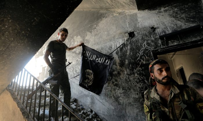 A member of the Syrian Democratic Forces calls his comrades during the fighting with Islamic State terrorists in Raqqa, Syria, Aug. 14, 2017.  (Reuters/Zohra Bensemra/File Photo)
