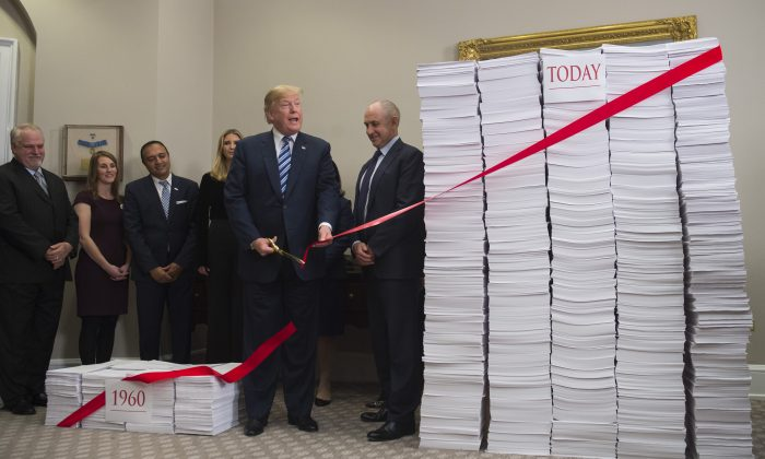 President Donald Trump cuts red tape draped between two stacks of papers representing the government regulations of the 1960s and the regulations of today, on Dec. 14. (SAUL LOEB/AFP/Getty Images)