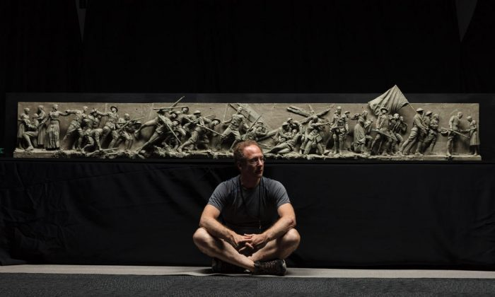 """Sculptor Sabin Howard sits with the maquette he created for """"A Soldier's Journey,"""" the sculptural component of the National World War I Memorial, at Weta Workshop in Wellington, New Zealand, in November 2017. (Courtesy of Sabin Howard)"""
