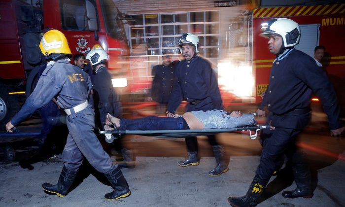 Firefighters carry a victim on a stretcher after a fire at a restaurant in Mumbai, India, Dec. 29, 2017. (Reuters/Stringer)