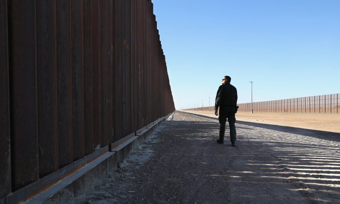 A Border Patrol agent at the U.S.-Mexico border fence in San Luis, Ariz., on Nov. 17, 2016. The U.S. government built triple fencing to deter illegal immigrants and smugglers who previously easily crossed the border there. (John Moore/Getty Images)