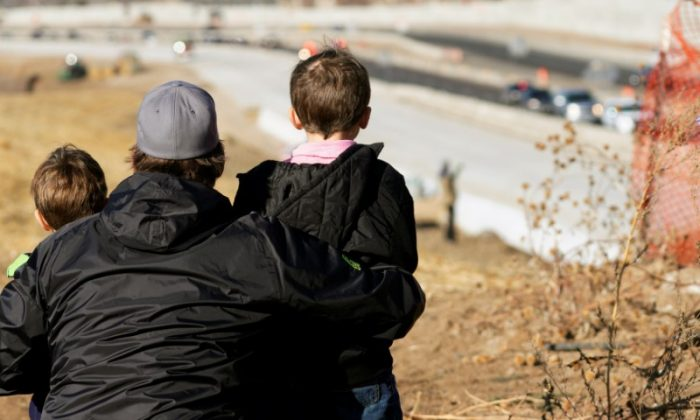 A man and two young boys watch a procession of police vehicles escort the hearse carrying the body of a deputy killed in a domestic disturbance where multiple deputies and civilians were shot in Highlands Ranch, Colorado, on Dec. 31, 2017. (REUTERS/Rick Wilking)