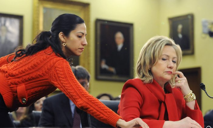 Then-Secretary of State Hillary Clinton (R) receives a note from her aide Huma Abedin (L) as she testifies about the State Department's budget during a hearing of the State, Foreign Operations, and Related Programs Subcommittee of the House appropriations committee on March 10, 2011. (Jonathan Ernst/Getty Images)