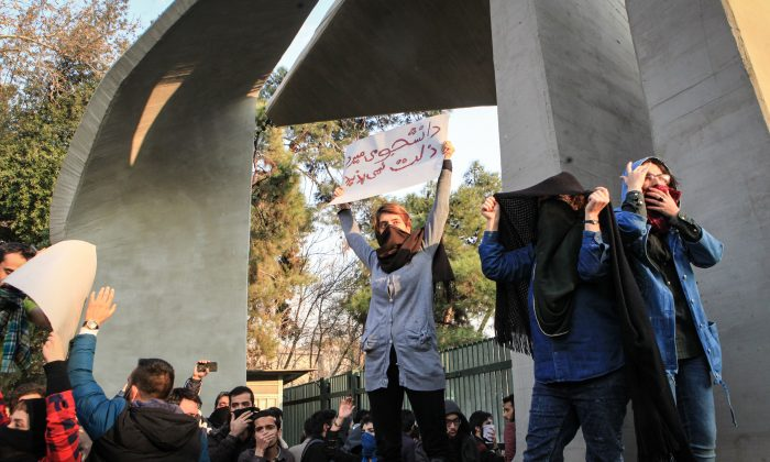 "Students protest the Iranian regime at the University of Tehran on Dec. 30, 2017. One of the students is holding a sign in Persian, which translates to, ""Students would rather die than accept oppression."" (STR/AFP/Getty Images)"