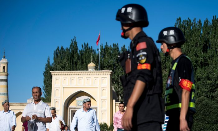 Police patrol the streets as Uyghurs leave the Id Kah Mosque in the old town of Kashgar in Xinjiang, on June 26, 2017. (Johannes Eisele/AFP/Getty Images)