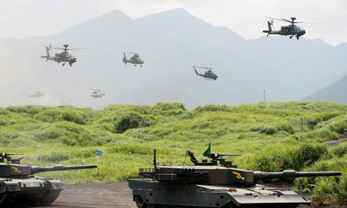 Ninety-type tanks move along with helicopters during a live-fire exercise for Japan's ground Self-Defense Force at the foot of Mount Fuji, on Aug. 21, 2008. Japan is considering weakening the constitutional limitations placed on its military forces. (KEN SHIMIZU/AFP/Getty Images)
