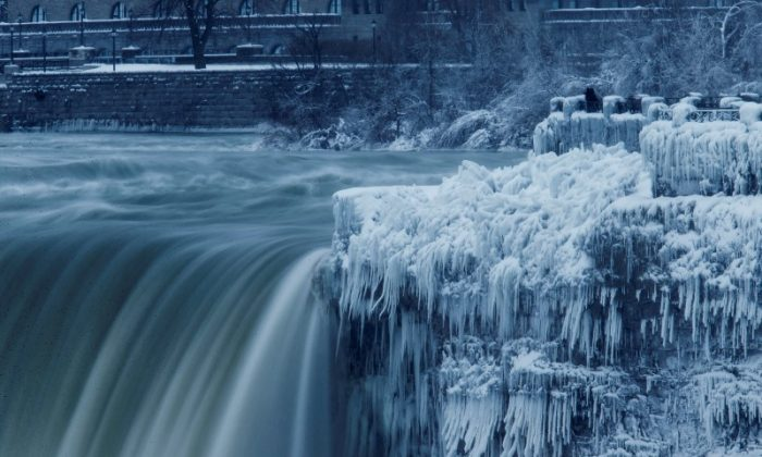 A lone visitor takes a picture near the brink of the ice covered Horseshoe Falls in Niagara Falls, Canada. (Aaron Lynett/Reuters)