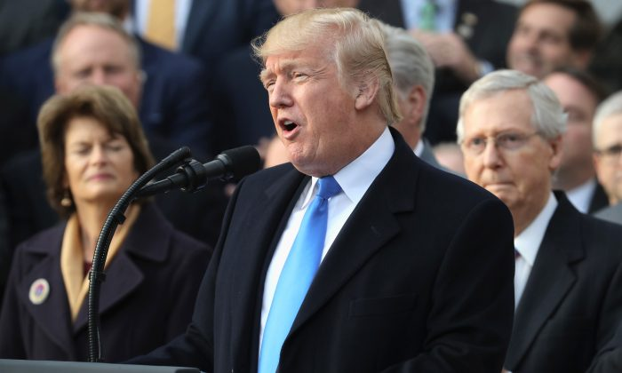 U.S. President Donald Trump, flanked by Republican lawmakers, celebrates Congress passing the Tax Cuts and Jobs Act on the South Lawn of the White House on Dec. 20, 2017 in Washington, D.C. The biggest threat to the Canadian economy comes from companies already operating in both countries that may move more operations to the United States. (Chip Somodevilla/Getty Images)